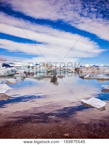 The ice floes and clouds of lagoon Jokulsarlon, Iceland. Cirrocumulus magically reflected in the smooth water of the lagoon. The concept of northern extreme tourism