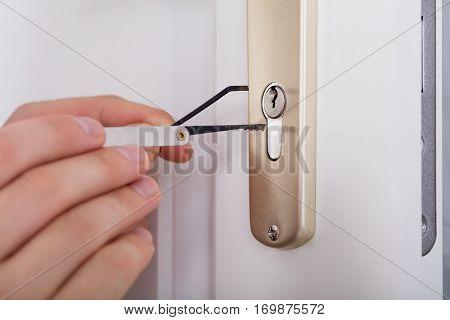 Close-up Of Lockpicker Hand Opening Door Lock