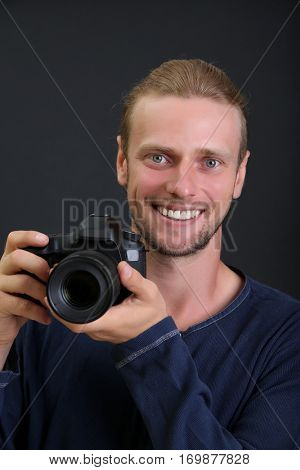 Handsome photographer with camera,isolated on black