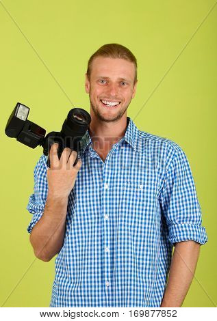 Handsome photographer with camera,on green background