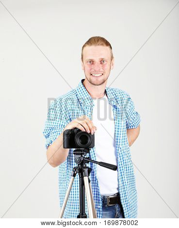 Handsome photographer with camera on tripod, on gray background