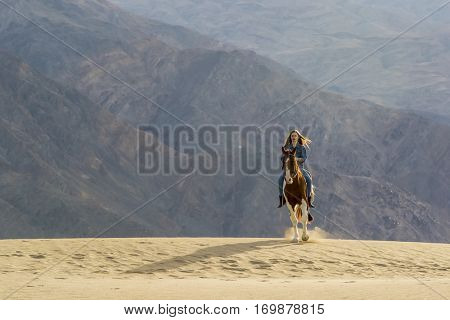 A female model riding her horse through the Mohave Desert