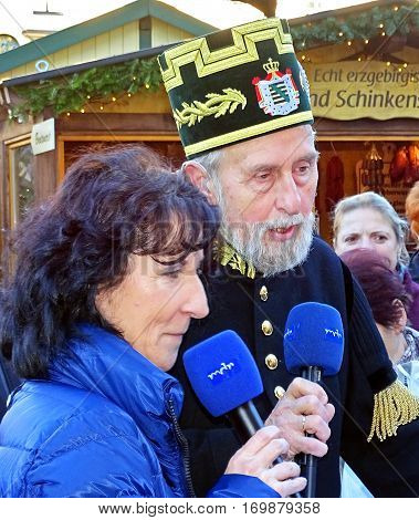 Annaberg-Buchholz, Germany - December 20, 2015: The presenter Heike Leschner and a man in traditional miner uniform comment for the TV channel Mitteldeutscher Rundfunk (MDR) the mountain parade in Annaberg-Buchholz (Saxony / Germany).