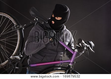 Person Wearing Balaclava Stealing A Bicycle On Black Background