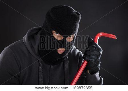 Portrait Of A Burglar Wearing Balaclava Holding Crowbar On Black Background
