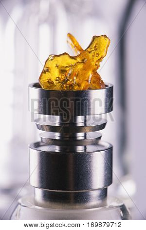 Piece of cannabis oil concentrate aka shatter over a titanium rig isolated over white background