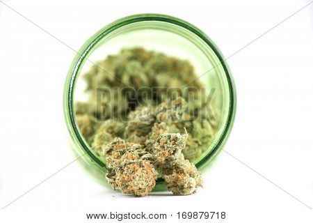Detail of cannabis buds (mango puff strain) on green glass jar isolated on white - medical marijuana concept