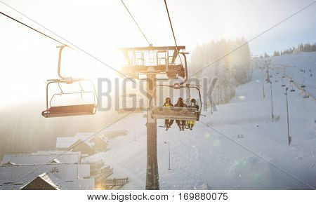 Three people are lifting on ski-lift in the mountains
