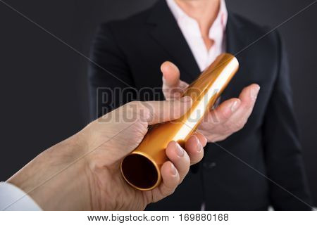 Close-up Of A Businessman Passing Golden Relay Baton To Colleague