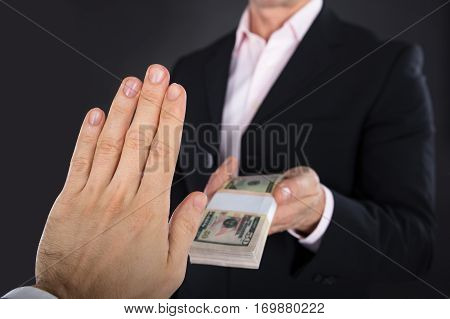 Close-up Of A Businessman Hand Refusing Bribe From A Partner On Black Background