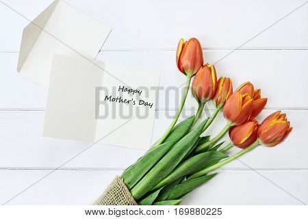 Overhead shot of a Mother's Day card and a bouquet of tulips over a white wood table top. Flat lay top view style.