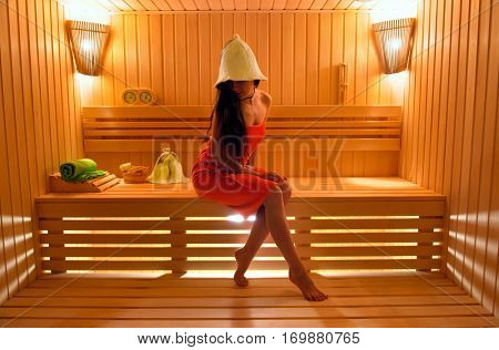 Beautiful girl in the hat for the sauna and steamed towel in the sauna. The new sauna of expensive wood
