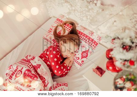 girl with long hair in red pajamas sleeping in bed