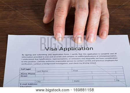 High Angle View Of Person Hand On Visa Application Form At Wooden Desk
