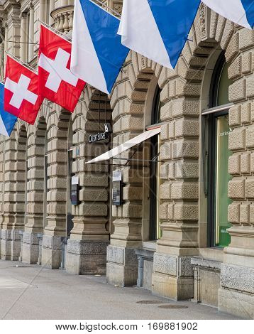 Zurich, Switzerland - 17 April, 2016: facade of the Credit Suisse headquarters building on Paradeplatz square, decorated with flags of Zurich and Switzerland. Credit Suisse Group is a Swiss multinational financial services holding company.