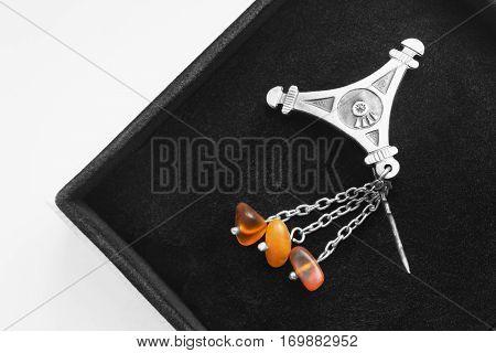 Vintage amber brooch in black jewel box closeup