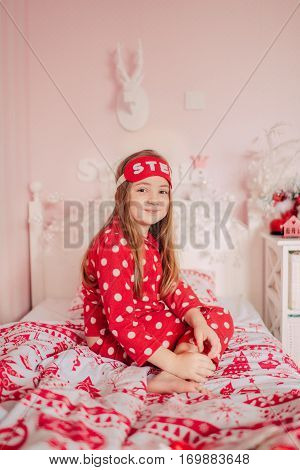 girl with long hair with a bandage to sleep in red pajamas sitting in bed