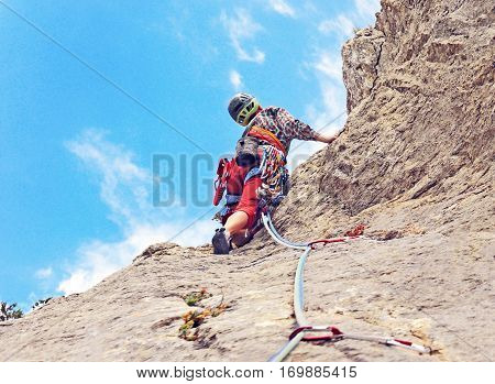 Young woman climbing in the Dolomits Italy. The rock-climber during rock conquest
