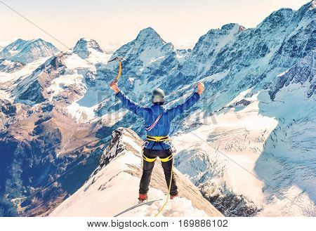 Climber reaches the summit of mountain peak. Climbing and mountaineering sport concep.