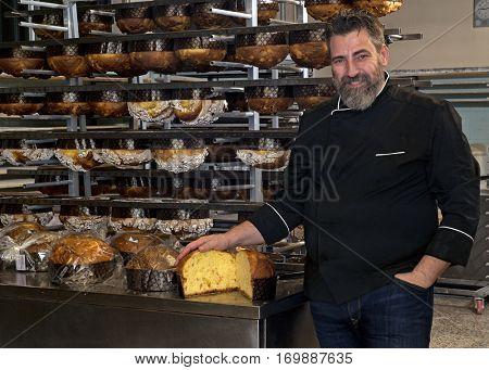 Baker portrait behind baked panettone kitchen shelf