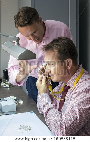 Two elegant man checking quality of diamonds by loupe and tweezers
