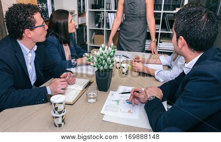 Teamwork looking to unrecognizable businesswoman in a meeting around of table in company headquarters