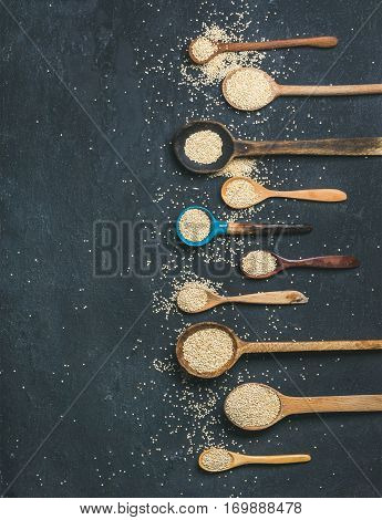 Quinoa seeds in different spoons over black stone background, top view, copy space. Superfood, healthy eating, dieting, clean eating, detox or vegetarian food concept
