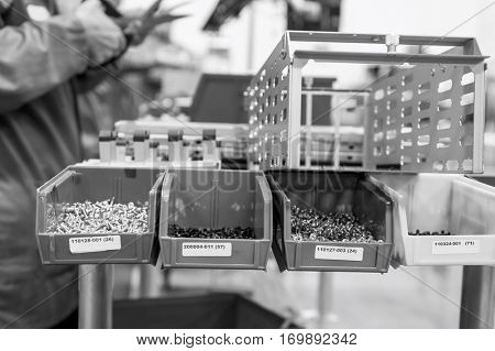 Variety of screws in tray with engineers working at electronics industry