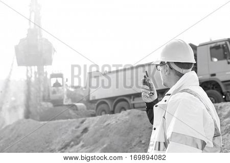 Side view of supervisor using walkie-talkie at construction site against clear sky