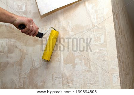 Male glue wallpaper - smooths the wall of wallpaper cut with glue