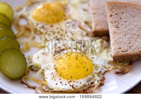 sunny side up eggs with onions on a plate with pickles and a slice of bread