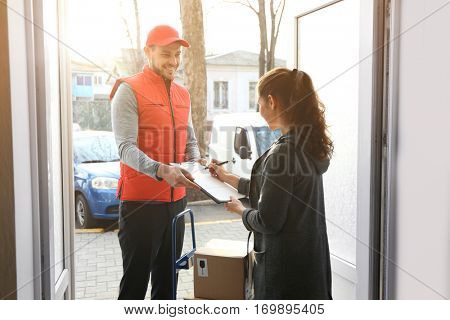 Young woman signing documents after receiving parcel from courier