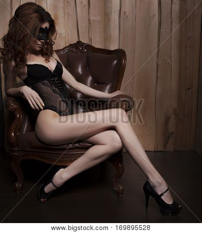 Sexy Woman In Black Lingerie, Mask And Heels On Luxury Brown Leather Chair