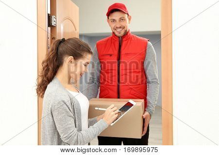 Young woman appending signature after receiving parcel from courier at home