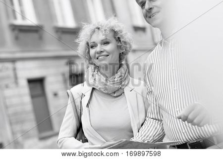 Happy middle-aged couple with map in city