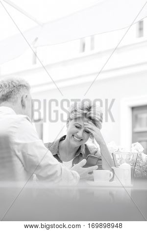 Happy middle-aged woman using mobile phone with man at sidewalk cafe