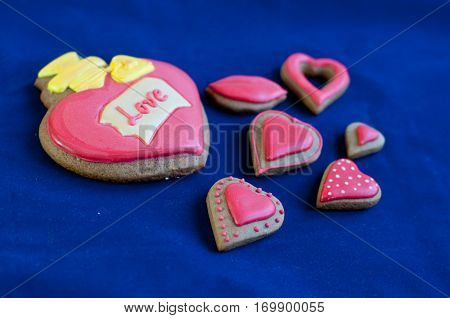 Composition of different size heart shaped honey cakes with rose glaze lay on blue background