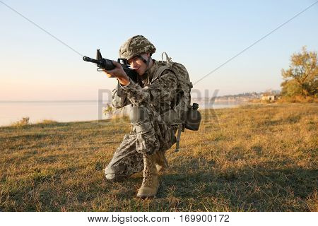 Soldier in camouflage taking aim at military firing range