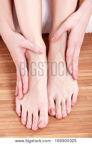 Female feet and hands on wooden floor