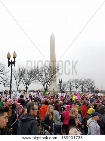 WASHINGTON DC - JAN 21, 2017: Women's March on Washington, marchers pass the Washington Monument in the background, in an anti-inauguration show of solidarity.