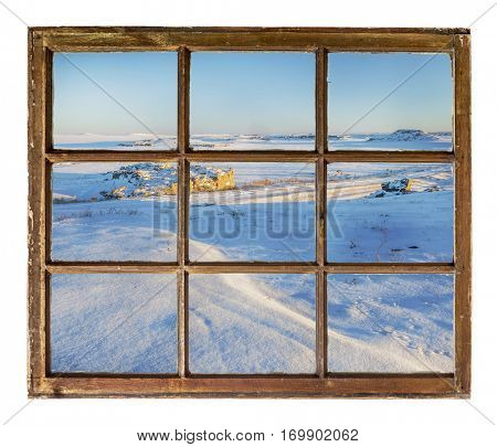 Winter scenery of northern Colorado prairie as seen  through vintage, grunge, sash window with dirty glass
