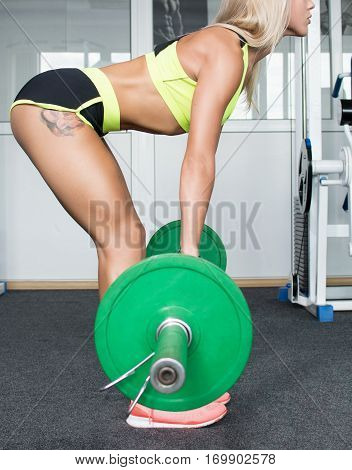 Active sport girl exercise on his back lifting heavy weights. Trainers. Shiny skin. Sports nutrition. Strength of will