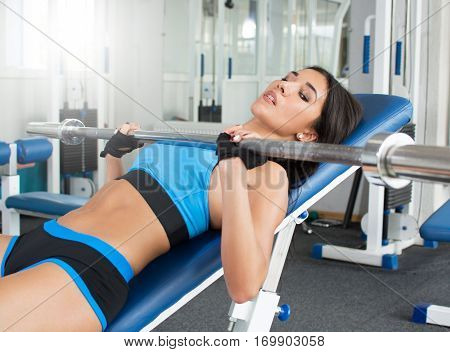 Woman doing workout in the gym lifting light weights. Psychological adjustment. Sports nutrition. Shiny skin.