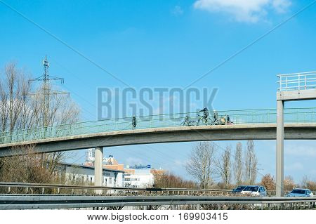 STUTTGART GERMANY - MAR 26 2016: People walking on pedestrian bridge passage above German autobahn highway on a spring warm day