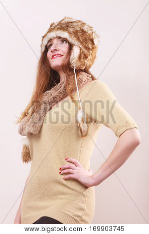 Winter fashion. Young woman wearing fashionable wintertime clothes fur cap woolen sweater studio shot on gray