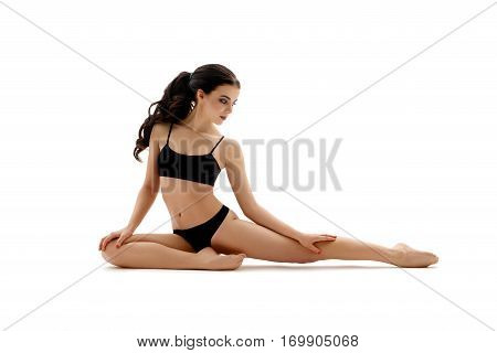 Beautiful young long haired brunette with nice make up in black sporty underwear posing gracefully studio portrait