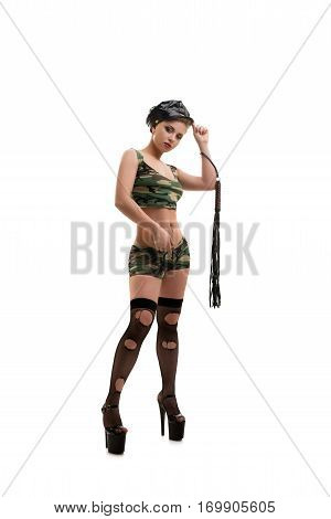 Sexy brunette in police cap, dazzle painted top and shorts, torn black stockings and platform shoes holding lash and handcuffs in her hands posing in studio