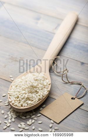 heap of white rice in wooden spoon on table with label for text.