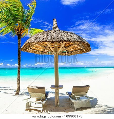 concept of perfect tropical holidays - white sandy beaches and umbrella with beach chairs  under palm tree