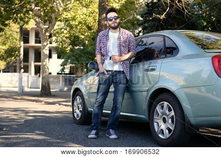 Successful young man with key standing near car